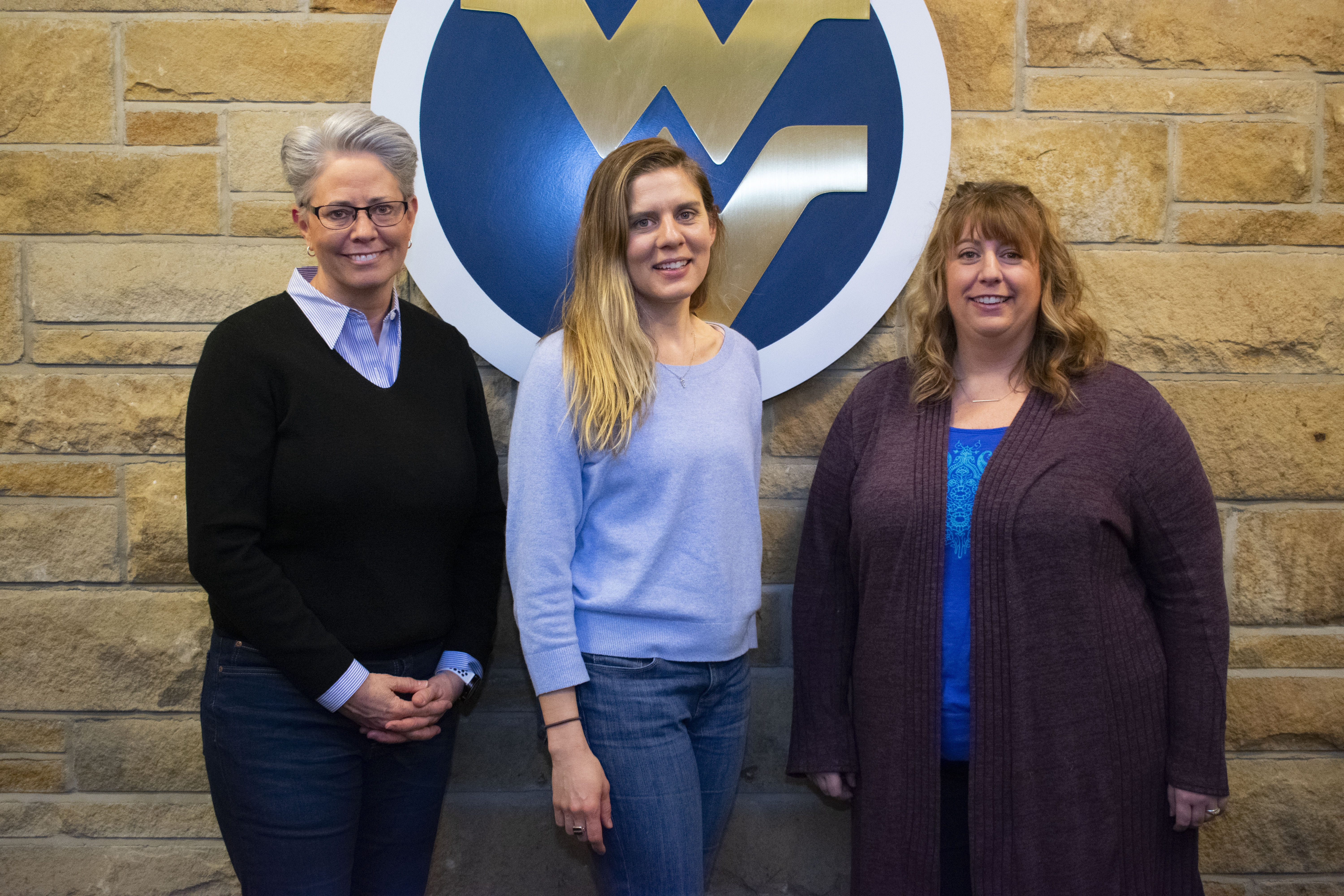 three women stand in front of flying WV logo